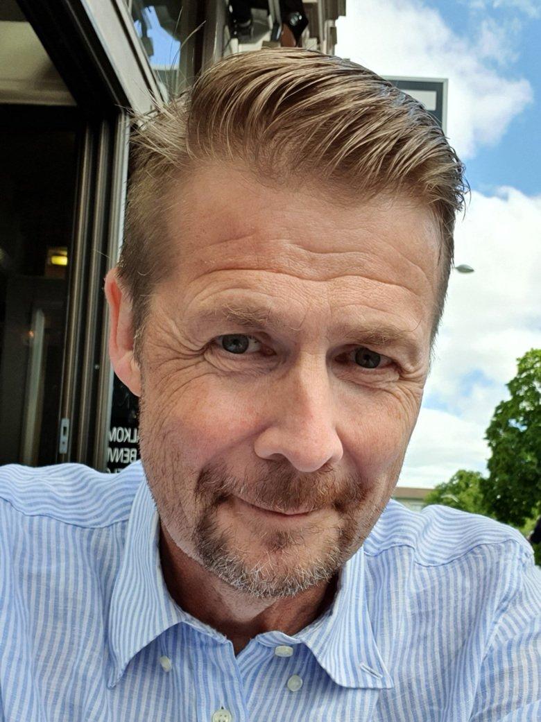Selfie på Erik Lundström som sitter utomhus.