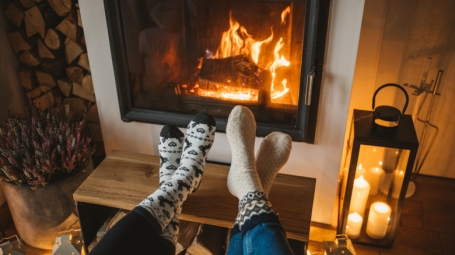 Two pair of stockinged feet by a cozy fire place.