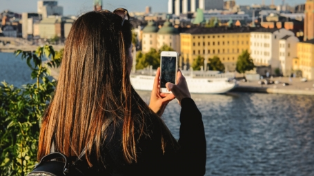 A student takes a photo of the Stockholm skyline with her phone.