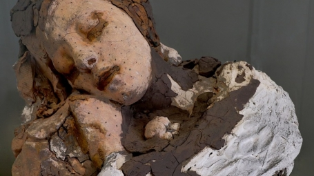 Photo of sculpture of sleeping human torso and head.