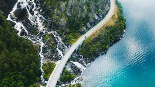 Drone panoramic photo of the car driving through picturesque road above the huge waterfall near the fjord in South Norway.