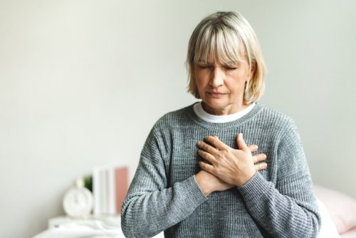 Woman with chest pain sitting on a bed