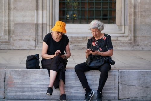 Two old women using their smart phones in  a vacation setting.