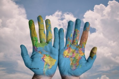 Hands with a world map painted on them.