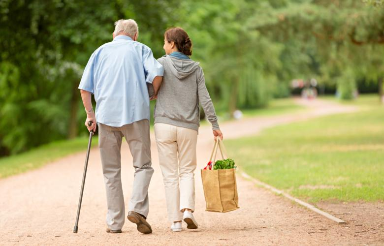 Photo of older man with a cane walking with woman.